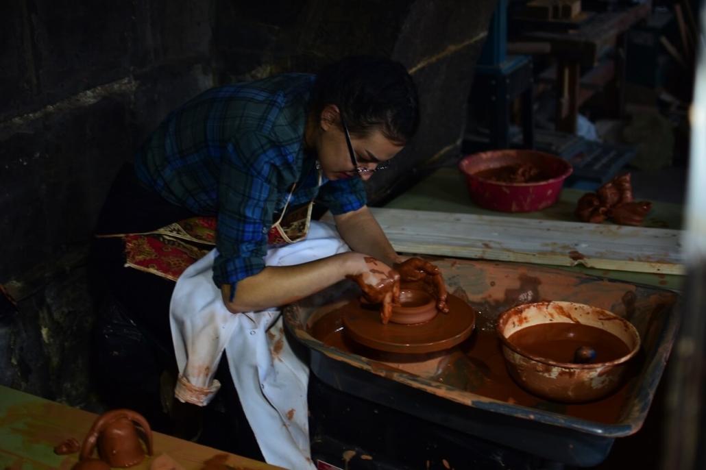 Une céramiste de l'atelier s'entraîne au tournage